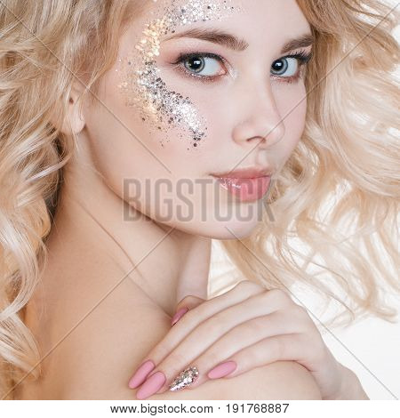 Cosmetics and manicure. Beauty women portrait of young curly blond woman with pastel manicure and perfect art make-up with glitter. Isolated. Studio
