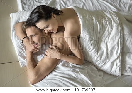 Cheerful nude couple under the white blanket on the bed. Guy holds his hands under the chin. Girl lies on his back. They both smiling. Closeup. Horizontal.