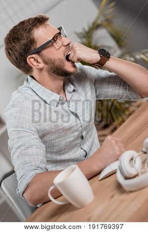 Stressed Caucasian Businessman In Eyeglasses Biting Fist And Sitting At Workspace