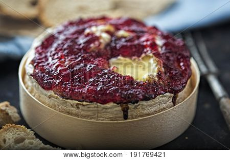 Baked camembert with cranberry sauce with fork