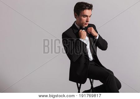 side view of an elegant young man fixing his bowtie while sitting on grey background
