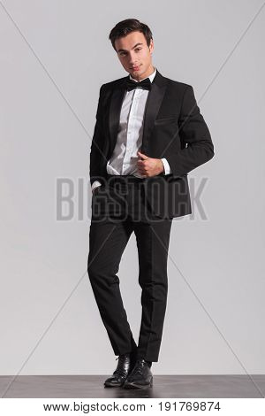 full body picture of an elegant young man in tuxedo and bowtie on grey background