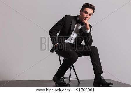 elegant man in tuxedo is sitting and thinking holding his chin on grey background