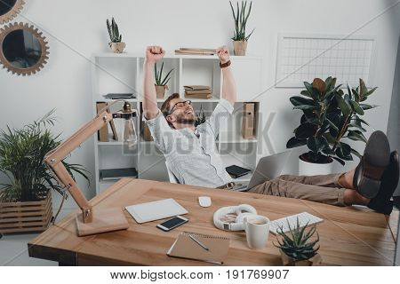 Cheerful Caucasian Businessman Sitting At Workplace And Using Laptop In Modern Office