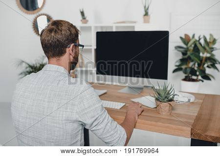 Back View Of Businessman Working With Computer At Workplace In Modern Office