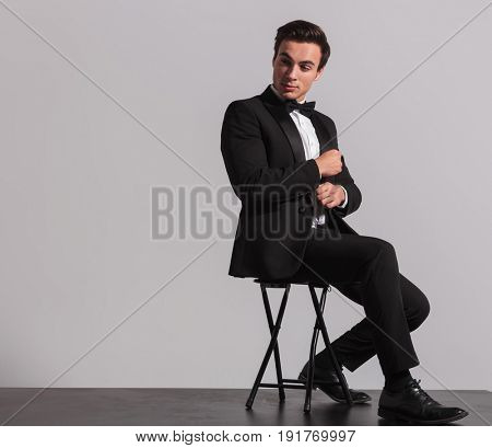 side of a seated elegant man fixing his sleeve and looks away on grey studio background