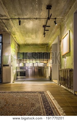Kitchen zone in a room in a loft style with shabby and brick walls. There is oven, chrome lockers, reticulated shelves, luminous yellow signboard and lamps, canvas, horizontal bar, carpet.