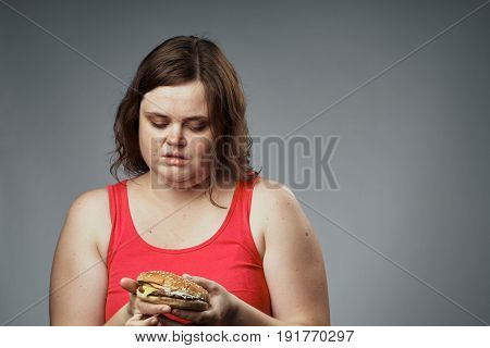 Hungry woman with a hamburger looking at a hamburger on a gray background studio.