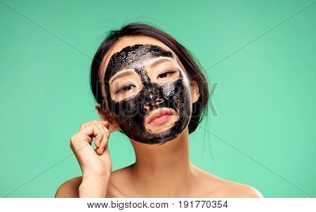 Woman in cosmetic mask, skin problem, facial treatment on green background portrait.