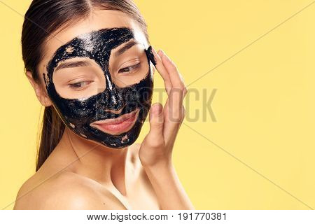 Woman in a cosmetic mask on a yellow background.