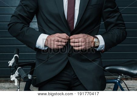 Cropped shot of stylish businessman sitting on bicycle and buttoning suit jacket