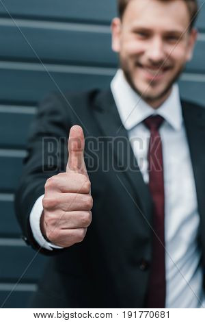 Close-up View Of Young Businessman Showing Thumb Up And Smiling At Camera
