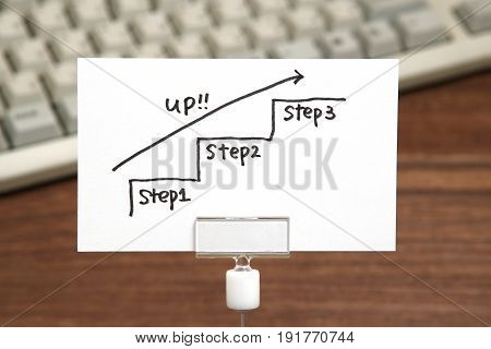 Handwriting stairs heading upwards with arrow on paper. Business success concept and growth idea.