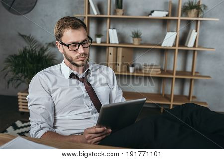 Pensive Businessman Using Digital Tablet While Sitting At Workplace