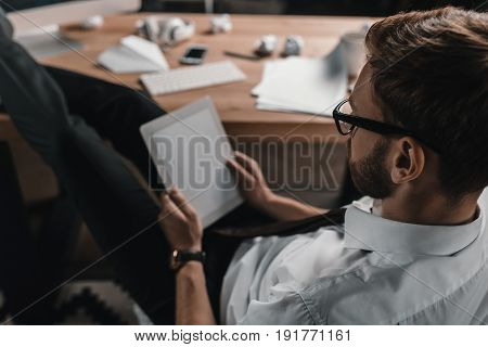 Focused Businessman Working With Digital Tablet While Sitting At Workplace In Office