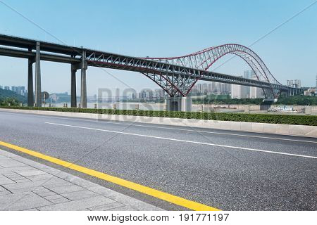 empty road near steel bridge near river in chongqing