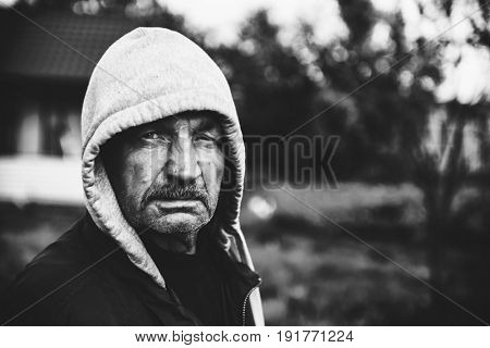 An elderly sad man in a hooded jacket. Black and white portrait
