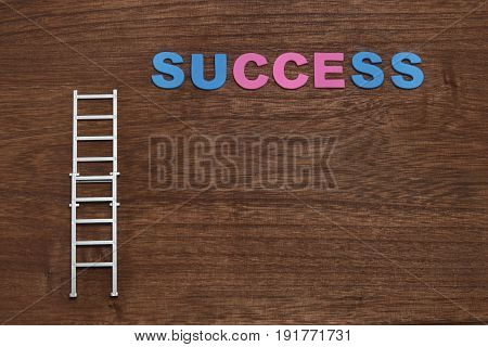 Career ladder with success words on wood. Business success concept and growth idea.
