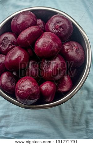 Cooked whole beetroots in bowl on blue background