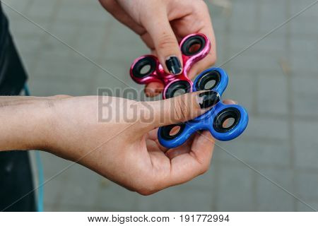 Girl with black nails play with fidget spinner stress relieving toy