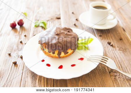 Chocolate Donut Or Bun With An Espresso On Table