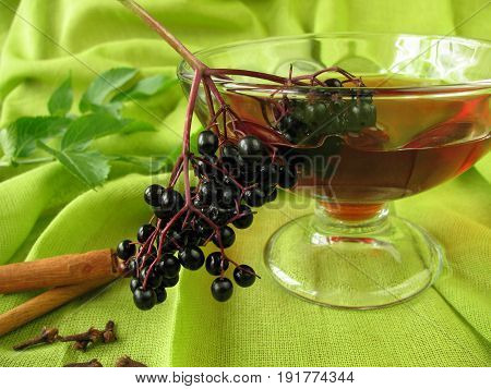 Glass of punch with black elderberries and cinnamon