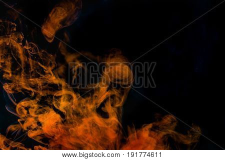Abstract background orange smoke texture in the air. Smoke fragments isolated on dark background.