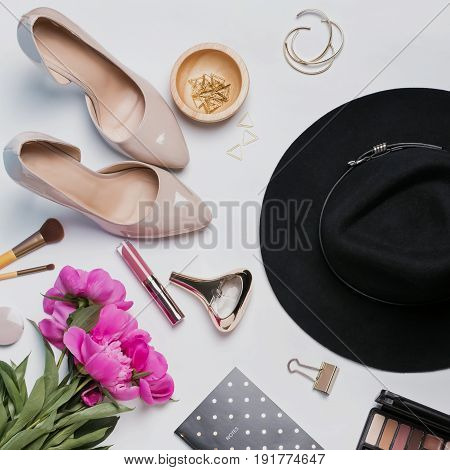 Stylish feminine accessories and pink peonies on white background, top view, square format