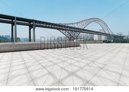 empty floor near steel bridge by river in chongqing