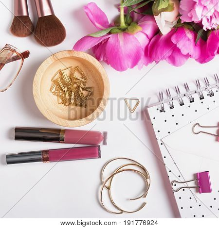 Gold and pink feminine accessories and peonies on the white background, top view