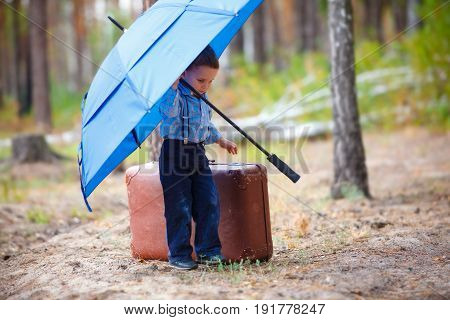 The boy stands in the middle of a pine forest near a vintage leather suitcase and holds a huge blue umbrella over himself