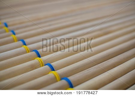 The pattern of many round wooden sticks woven with blue and yellow threads are closely related.
