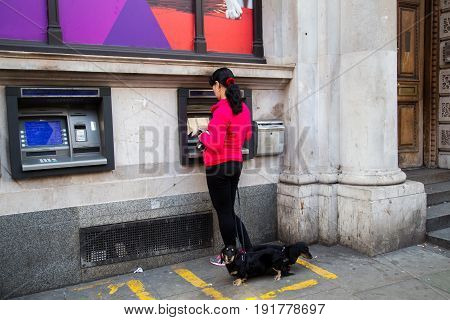 UK London - April 08 2015: A woman is standing by an ATM with dogs