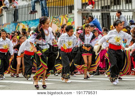 Banos De Agua Santa Ecuador - 29 November 2014: Group Of Unidentified Ecuadorian Kids In Traditional Colorful Costumes Dancing On Streets Of Banos De Agua Santa South America On November 29 2014