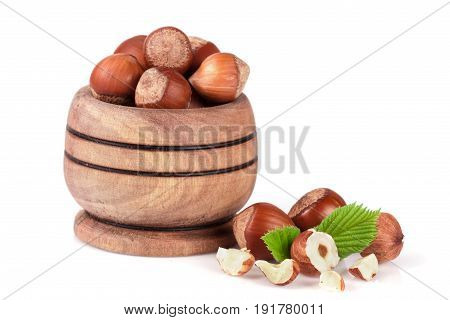 Hazelnuts with leaves in a wooden bowl isolated on white background.