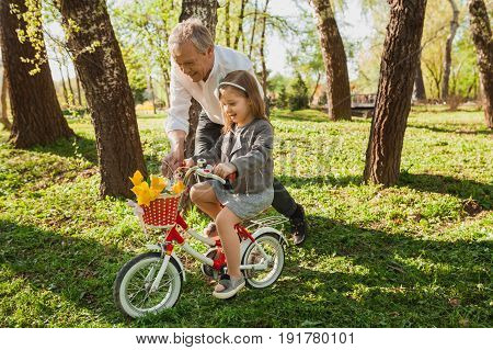Senior adult man learning granddaughter to ride a bicycle in the park.