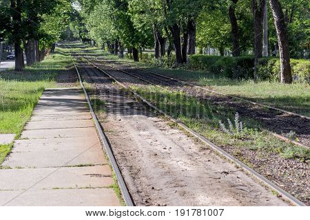 Looking down the tracks. Railroad tracks in the lush forest area of the town destination