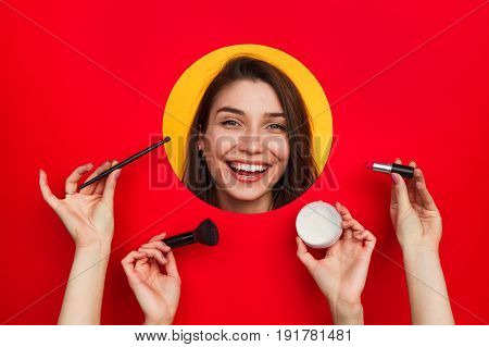 Woman smiling at camera out of circle while crop female hands holding cosmetics and brushes.