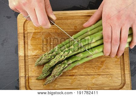 Woman Hands Cutting Asparagus On Wooden Board
