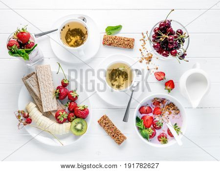 Delicious healthy fitness breakfast with granola and fruits for two, loose tea, bars, topview