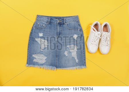 Blue denim shorts with white shoes isolated –blue and yellow background