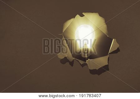 The concept of a new idea. Image of a glowing electric bulb on background of a hole in the paper.