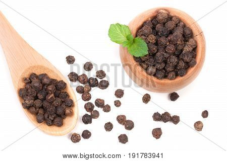 Black peppercorn in a wooden bowl and spoon isolated on white background. Top view.