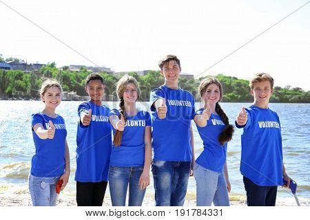 Young people standing on beach near river and showing thumbs up. Volunteering concept