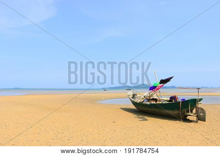 Beautiful blue sky on the wooden fishing boat on a sand beach