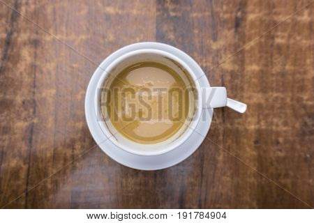 View on a white Cup of Coffee on a brown wooden Table. Close-up of a creamy Coffee with refreshing effect .Fresh Cup of Coffee. Coffee Break.