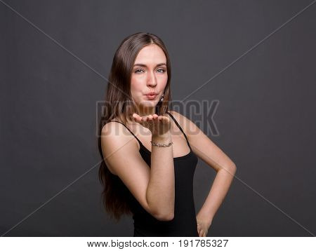 Attractive beautiful woman showing air kiss. Confident girl flirting with you, looking at camera.