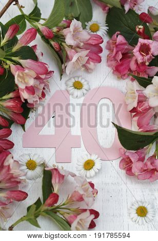 Pale pink paper cut number forty surrounded by spring flowers on a white wooden background