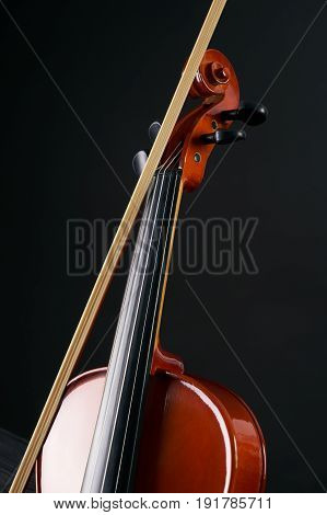 Close-up details of Violin with violin bow isolated on black background with copy space. Cello scroll on headstock and tuning pegs.