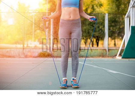 Low Section Of Sportswoman With Skipping Rope Standing On Stadium